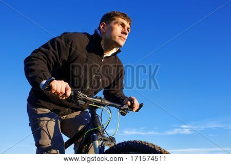 Portrait of cyclist from below at sky background. Man holds the handlebars of a bicycle on a sky background. Biker on bike against blue. Clouds. Healthy lifestyle. Spring season. Countryside.