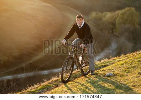 Cyclist Riding the Bike on the Beautiful Spring Mountain Trail. Landspace with hill and pathes. Travel in countryside. Healthy lifestyle.