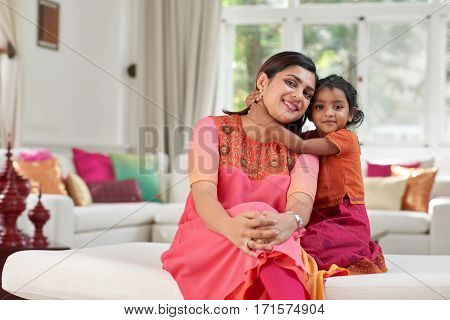 Joyful middle-aged woman in colorful traditional Indian clothes leaning to her little daughter while posing for photography