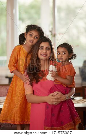 Portrait of lovely Indian family: beautiful middle-aged mother with her pretty little daughters posing for photography in living room