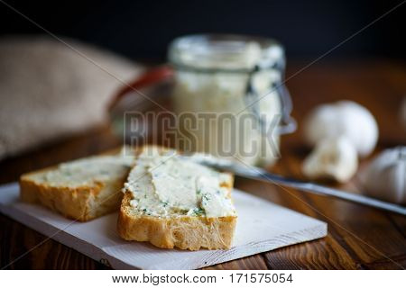 Fried toast with cheese pasting with herbs and garlic on a dark table