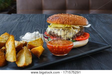 Fast food restaurant dish on served table. Meat cheese burger, potato chips and wedges. Take away set on dark black wood background. Hamburger, mayonnaise and spicy tomato sauce. Filtered