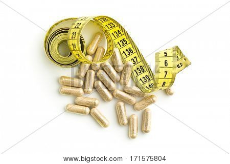 Capsules and measuring tape. Diet concept.