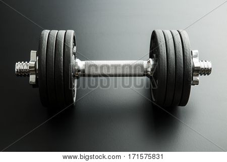 The metal dumbbell on black background.