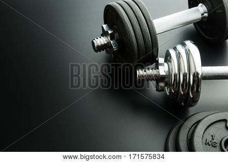 The metal dumbbell and weights on black background.