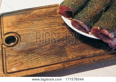 Fresh trout with spices and seasoning on the cutting board.