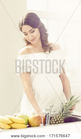 Beautiful pregnant woman with fruits in kitchen. Motherhood, pregnancy, maternity concept.