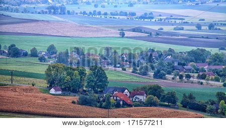 Hilly rural scene with some houses and village in light blue fog