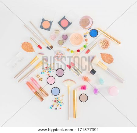 Colorful make up and brushes flat lay top view scene on white background