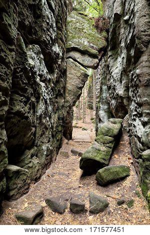 Big gray stone block tilted between tall rock walls