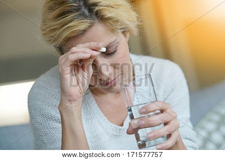 Middle-aged woman at home taking pill to ease headache