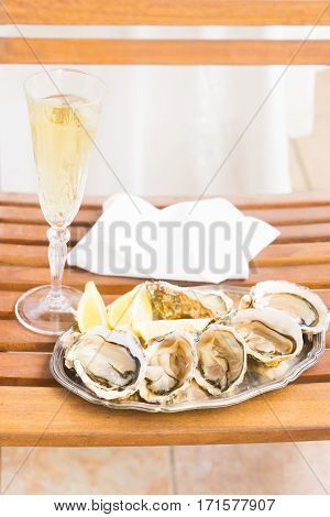 Raw oysters shells plate and glass of champagne