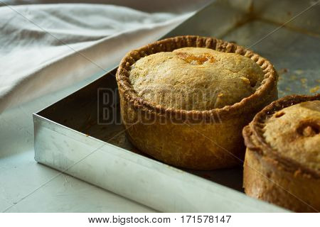 Freshly baked homemade English pork pies with golden crust on aluminum baking tray close up selective focus
