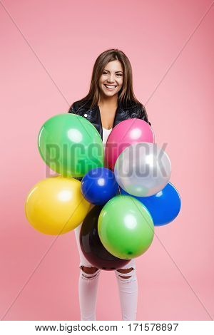 Trendy woman in ripped jeans and fashion leather jacket smiles holding bunch of helium balloons