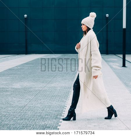Fashionable stylish Looker girl in white cap and knit coat. Walks on the Europe street. Outdoor. Streetstyle.