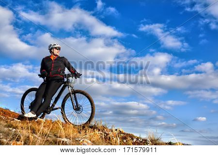 Cyclist in Black Jacket Riding the Bike Down Hill. Extreme Sport Concept. Space for Text. Cyclist in the helmet and black sunglasses. Background with blue sky and clouds. Bicycle riding in the countryside.