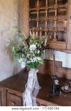 Wedding bouquet with white flowers and greenery on a wooden cupboard