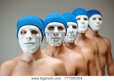 The people in masks on gray studio background. the concept of human commonality and individuality