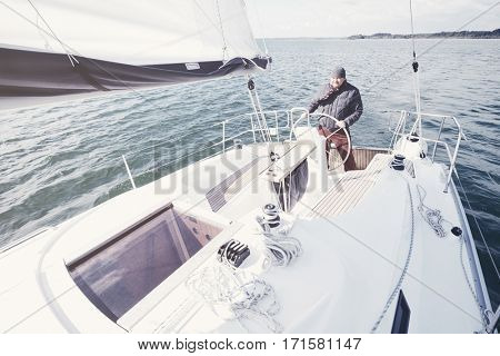 Senior man wearing jacket, scarf and hat, standing on yacht steering wheel and enjoying perfect autumn day under sails - sailing holidays concept
