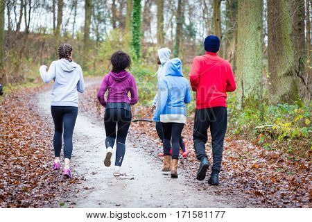 Fitness trainer guiding group of four determined young people during jogging in the forest