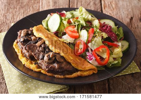 Austrian Cutlet With Mushrooms, Scrambled Eggs And Vegetable Salad Close-up. Horizontal