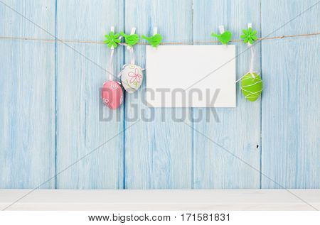 Colorful easter eggs and greeting card in front of wooden wall