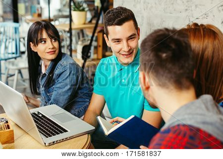 Group of students learning in a cafe with a laptop on the table in front of them