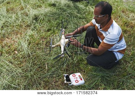 Profile view of Indian man launching quadcopter while spending free time in park, remote controller lying on grass