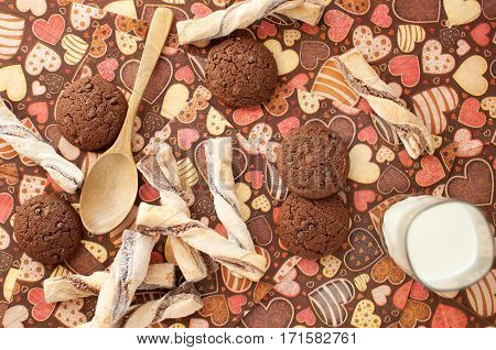 Glass of milk and cookies on dark napkin with image of hearts close up. Top view.