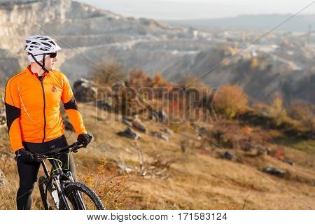 Cyclist Riding the Bike Down Rocky Hill. Extreme Sport Concept. Space for Text. Cyclist in Orange Jacket, helmet and blacksunglasses. LAndscape with hill and rocks. Travel in the countryside.