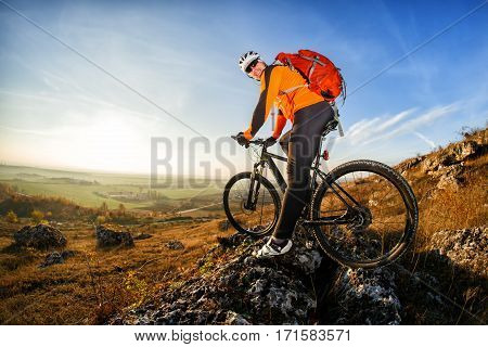 Cyclist in helmet and glasses on mountain bike stands on the precipice of hill under blue sky and sun. Wide angle view. Cyclist in Orange Jacket, helmet, sunglasses and with red backpack. Spring season. Countryside. Fisheye.