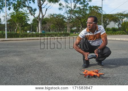 Small quadcopter standing on asphalt while its owner sitting on haunches and holding remote controller in hands