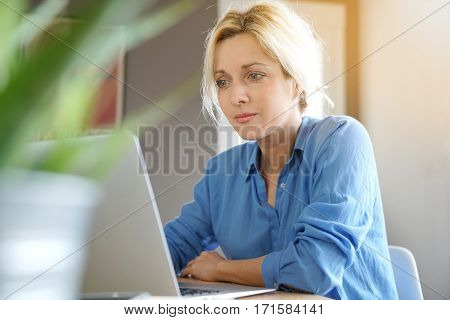 Portrait of blond woman with blue shirt working from home on laptop