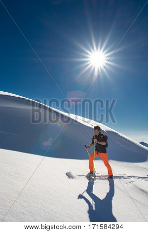 A Man Alpine Skier Climb On Skis And Sealskins In A Strong Sunny Day