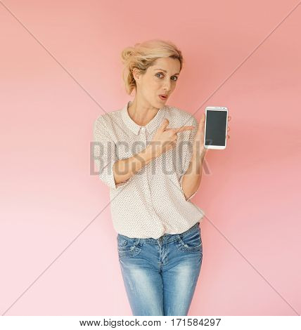 Blond woman on pink background showing smartphone screen