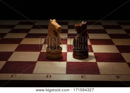 Wooden chess. Black and White Knight on chess board.
