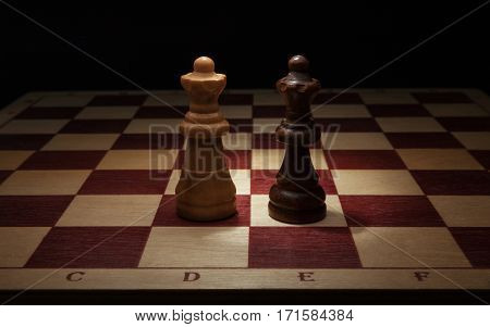 Wooden chess. Black and White Queen on chess board.