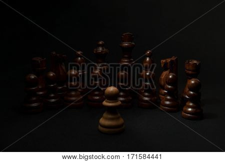 Chess. White pawn and Black figures on black background. Set of black figures. Background for presentation.