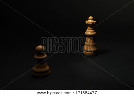 Chess. White Pawn and Queen on black background.
