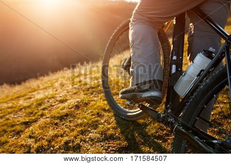 closeup of rear wheel sports bike. race mountainbike on the hill. Legs. Shoes. Detail of the bicycle. Wheel and bottle. Green field and grass. Travel in the countryside. Spring season.