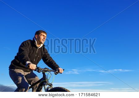 Portrait of cyclist seen from below with blue sky. Hands. Detail of the bicycle. Helm. Healthy lifestyle. Landscape. Spring season. Travel in the countryside.