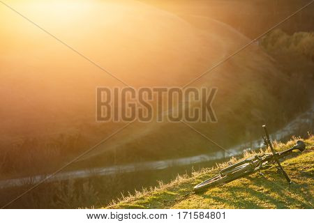 Mountain bicycle is on the hill with green grass on sunset background. Landscape with hill and green field. Evening. Spring season. Travel in the countryside.