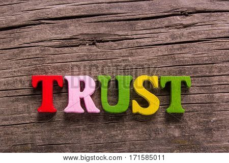 trust word made from colored wooden letters on an old table. Concept