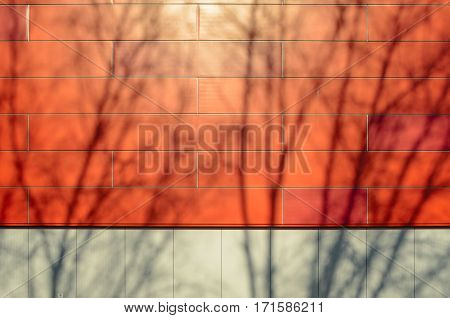 The front facade of a modern building of gray and red panels. Shadows of the trees on the facade of the building. Architectural background.