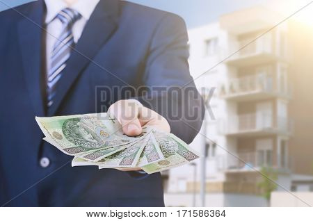 Money loan polish pln cash banknote apartment flat concept. Polish businessman holds money. The loan on the house.