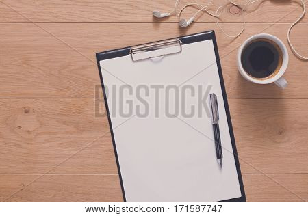 Mockup for check list, empty note paper, notepad with pen and coffee cup on brown wood background, top view with copy space. Office, writer or study concept