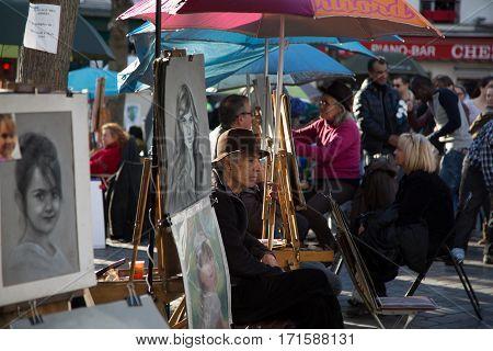 PARIS, FRANCE - MARCH 8, 2015: Artists and artworks on Place du Tertre in Montmartre. Portrait of the painter.