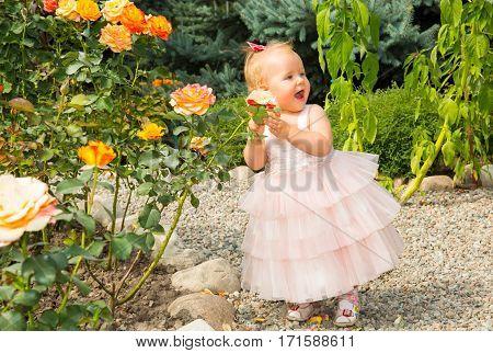 Happy pretty girl kid celebrate her birthday with rose decor in beautiful garden. Positive human emotions feelings joy.