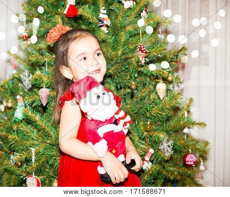 Portrait of fazakh asian child girl around a Christmas tree decorated. Kid on holiday new year