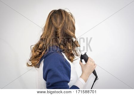 Young beautiful woman using modern hair curling iron to make new stylish hairstyle.